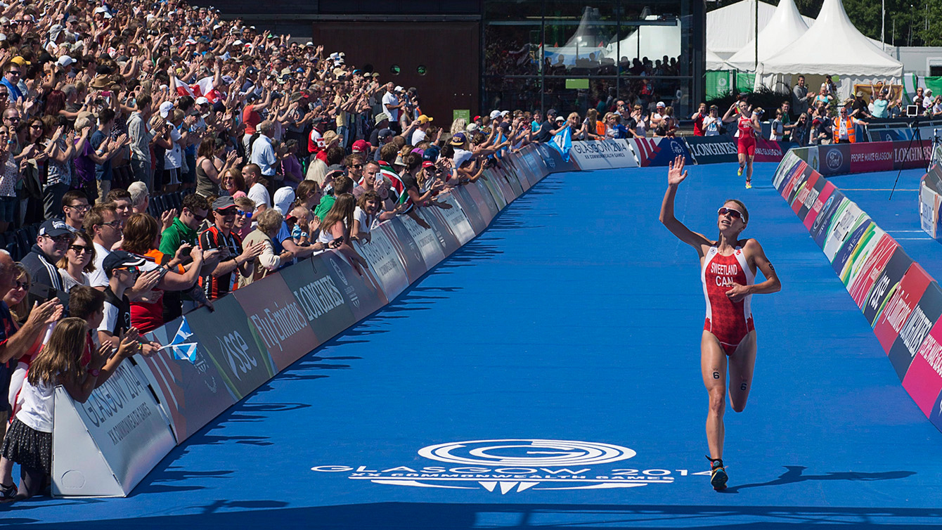 Canada's Kirsten Sweetland from Victoria, B.C., races to a silver medal in the women's triathlon at Strathclyde Country Park in Glasgow, Scotland on Thursday, July 24, 2014. The medal is Canada's first at the Games. (THE CANADIAN PRESS/Andrew Vaughan)