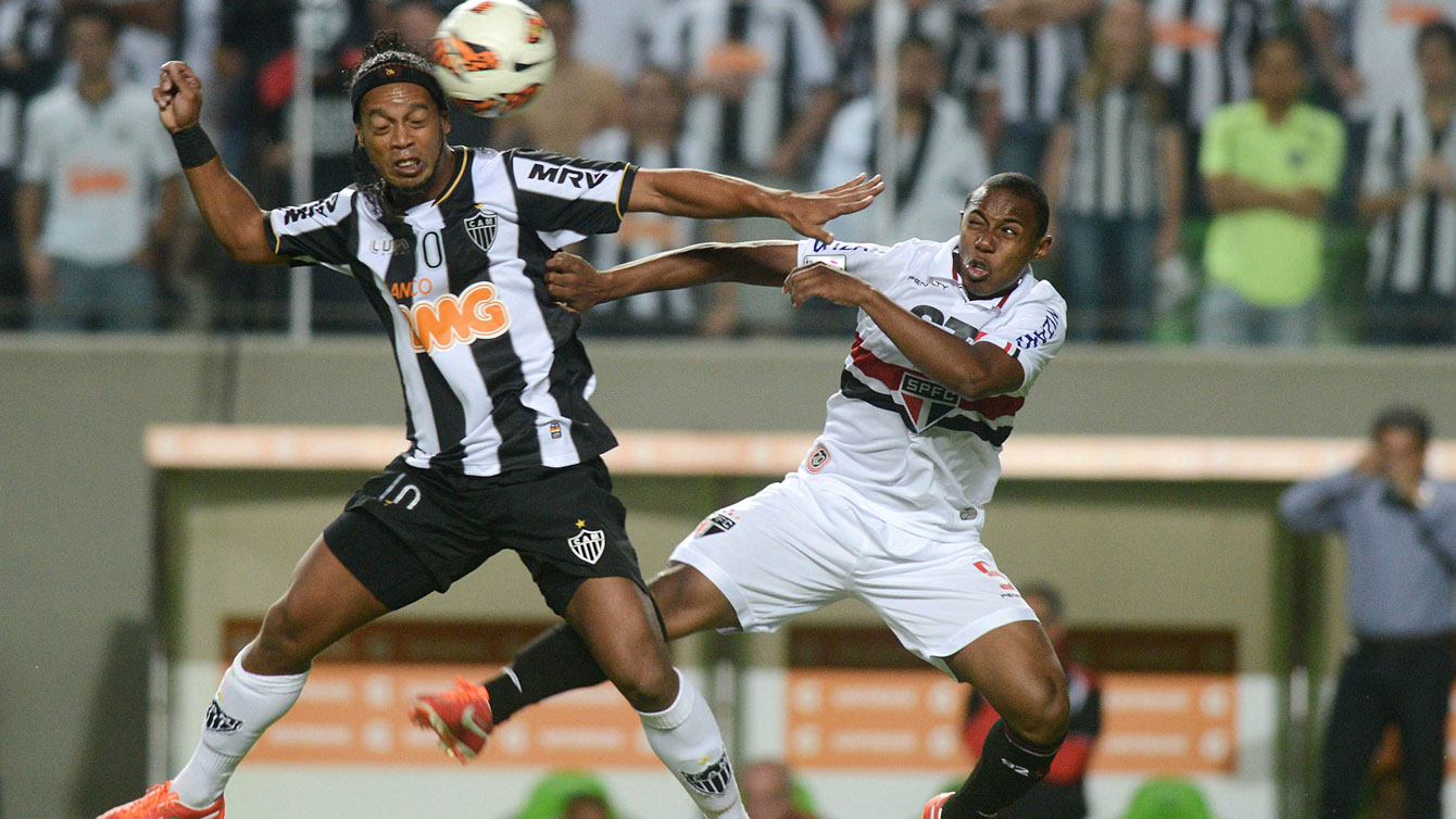 Ronaldinho of Brazil's Atletico Mineiro, left, fights for the ball with Wellington of Brazil's Sao Paulo FC at a Copa Libertadores soccer match in Belo Horizonte, Brazil, Wednesday, May 8, 2013
