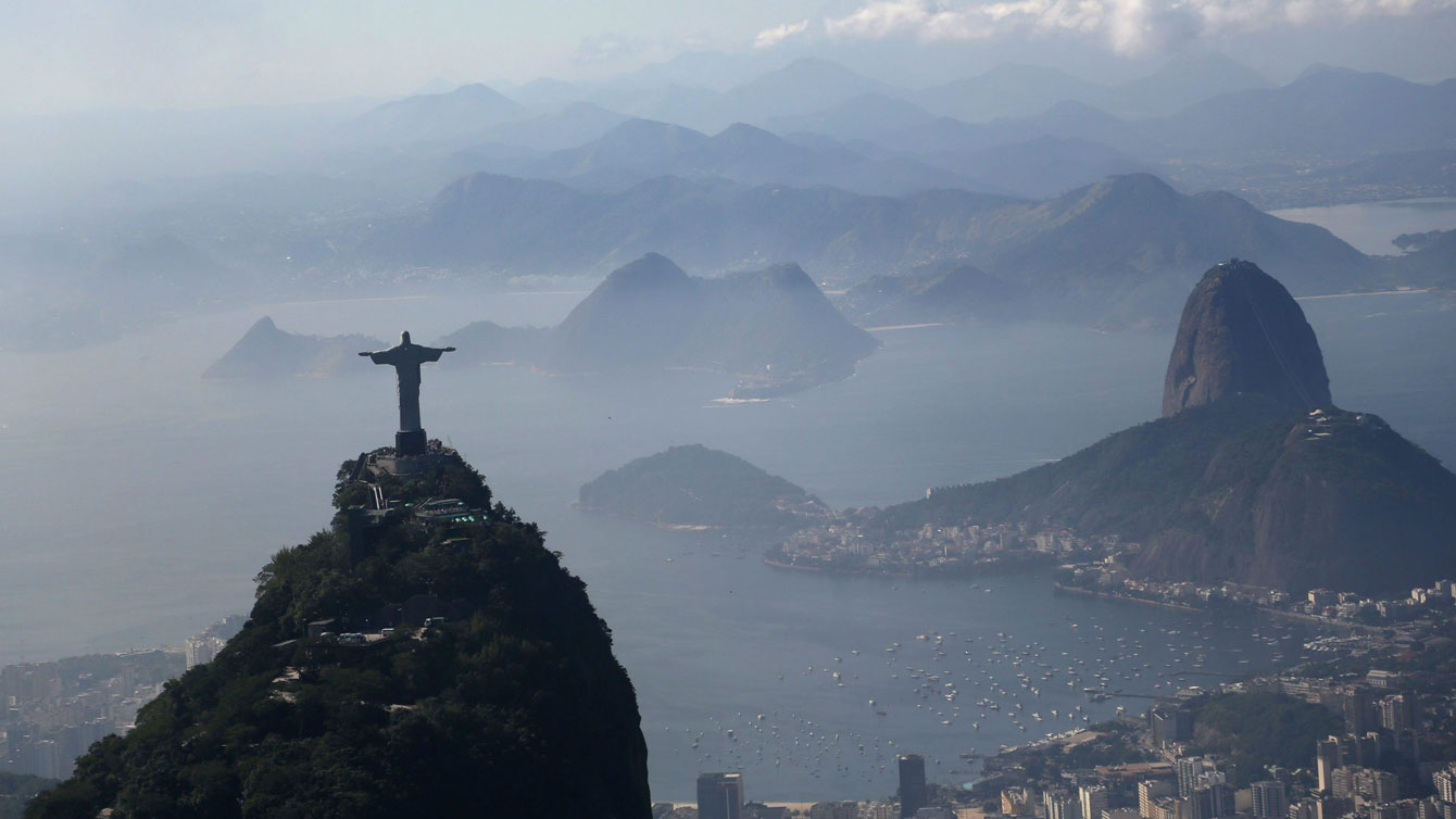 Christ the Redeemer statue stands above Rio de Janeiro, Brazil. Sugarloaf Mountain is at right.