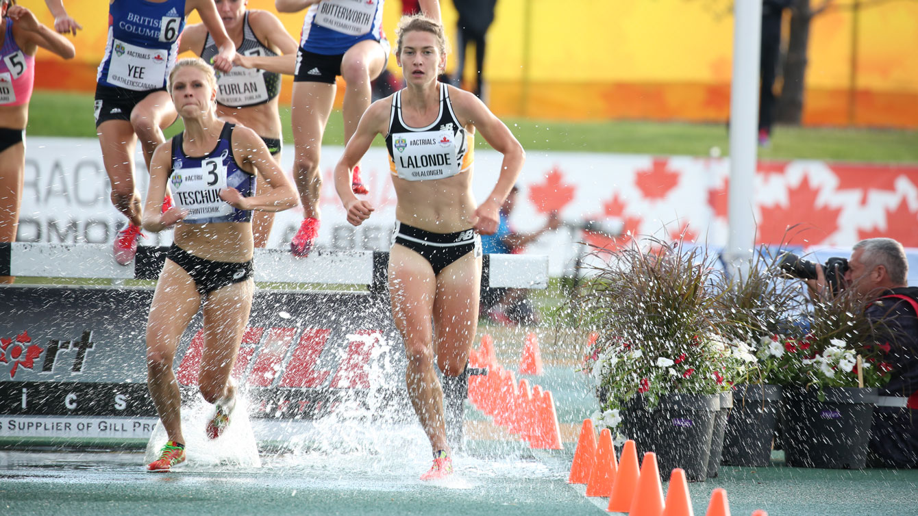 Erin Teschuk and Genevieve Lalonde clear the water hazard in the women's steeplechase at Olympic trials on June 8, 2016. Teschuk won the race, with Lalonde third.