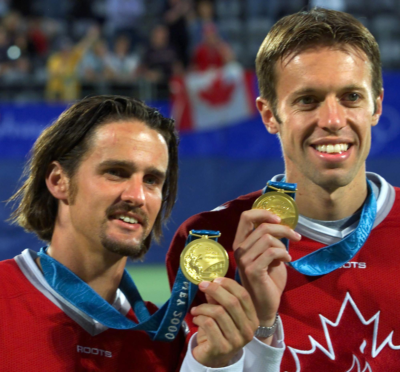 Sebastien Lareau (left) and Daniel Nestor of Canada hold up their gold medals after winning them in men's doubles tennis at the Olympic Games in Sydney Australia Wednesday Sept 27, 2000. (CP PHOTO/Tom Hanson)