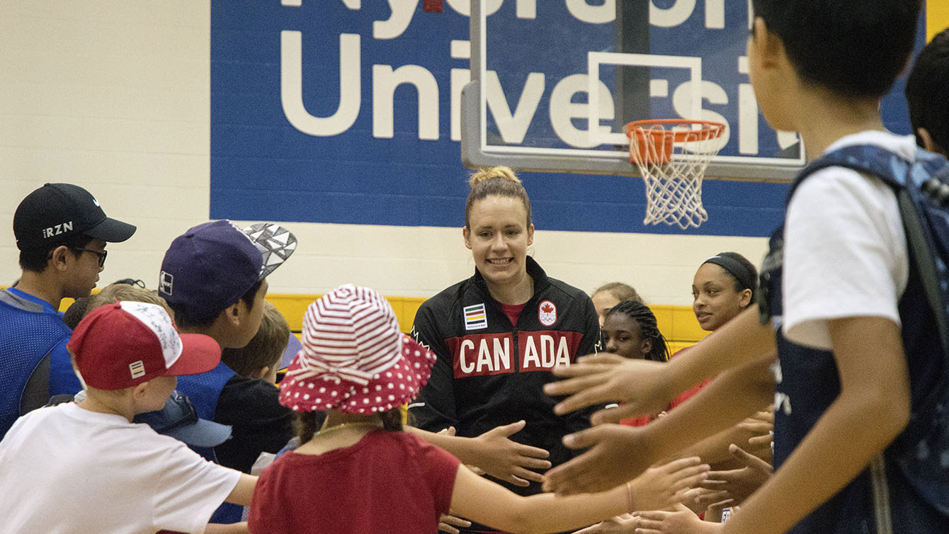 Shona Thorburn runs through a crowd of children before heading onto the stage for the Team Canada basketball announcement on July 22, 2016. (Tavia Bakowski/COC)