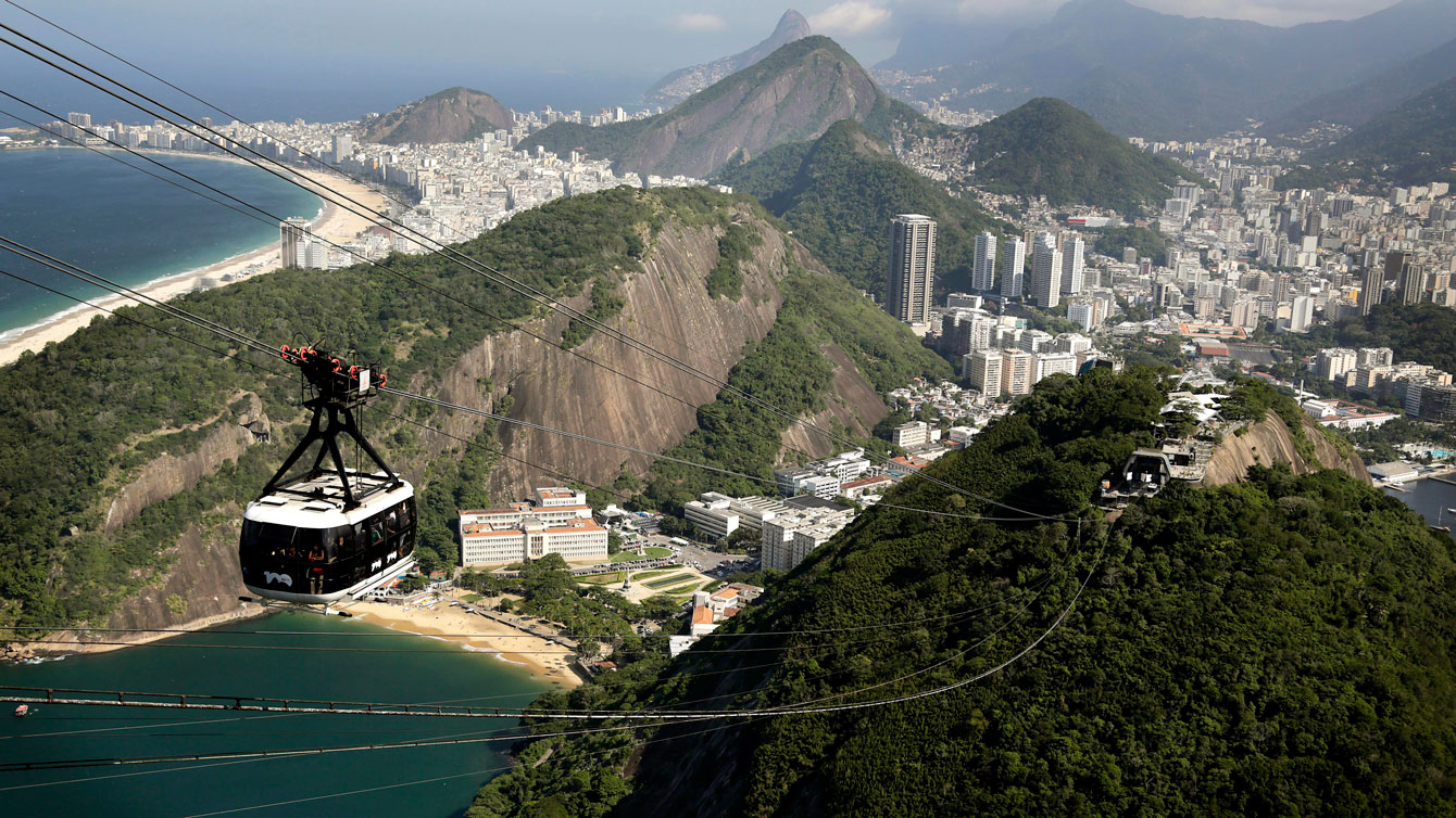 A cable car seen from the iconic Sugarloaf mountain is dwarfed by the backdrop of Rio de Janeiro, Brazil, Monday June 9, 2014.