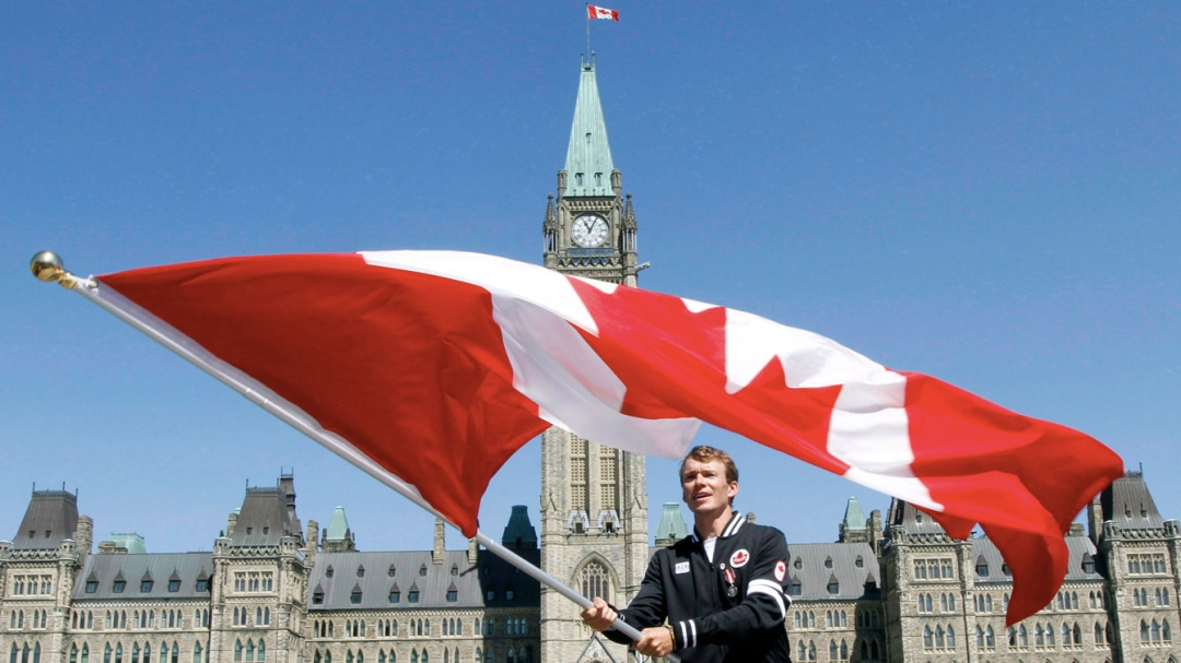 Simon Whitfield with the Canadian flag on Parliament Hill