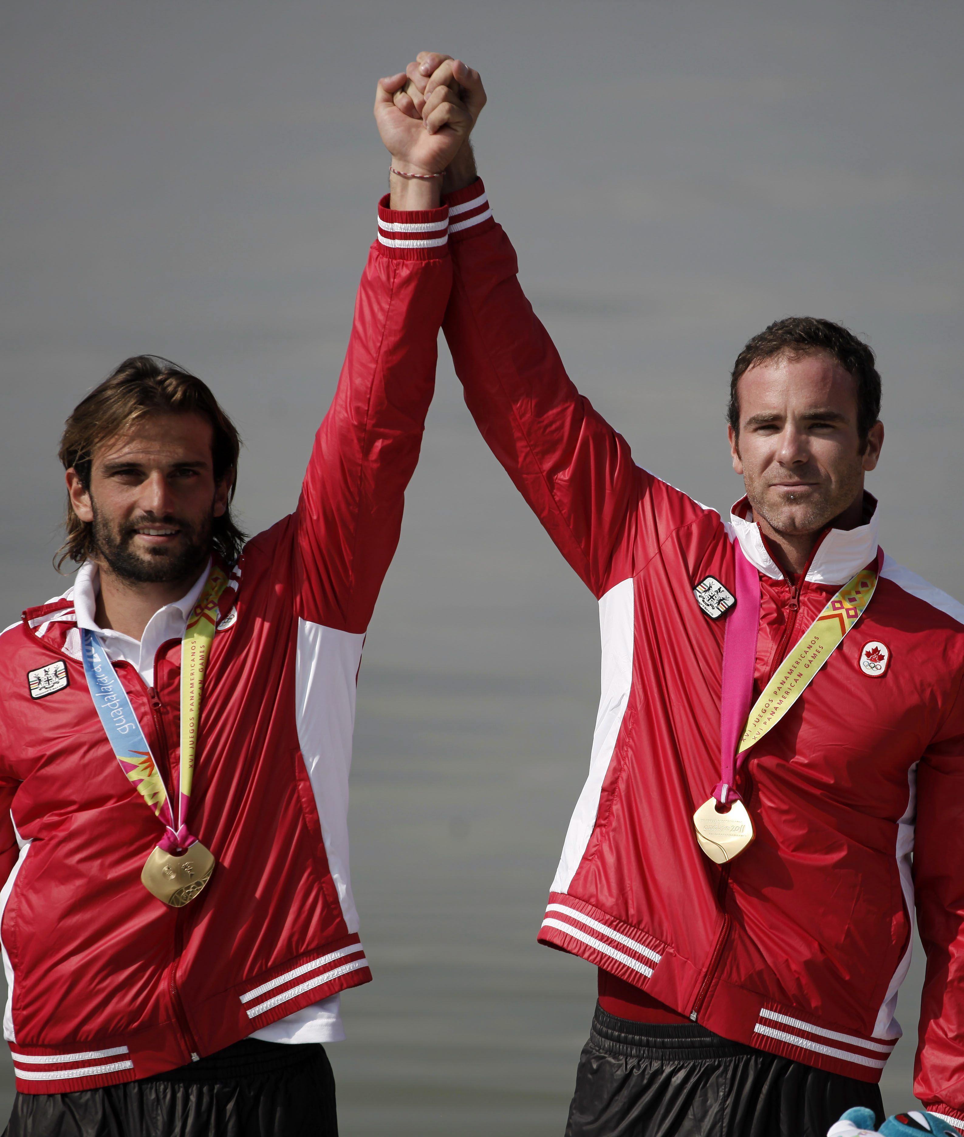 Gold medal winners Hugues Fournel, left, and Paul Cochrane from Canada celebrate on the winner's podium during the awards ceremony for the men's double K2 200m kayak event at the Pan American Games in Ciudad Guzman, Mexico, Saturday Oct. 29, 2011. (AP Photo/Eduardo Verdugo)