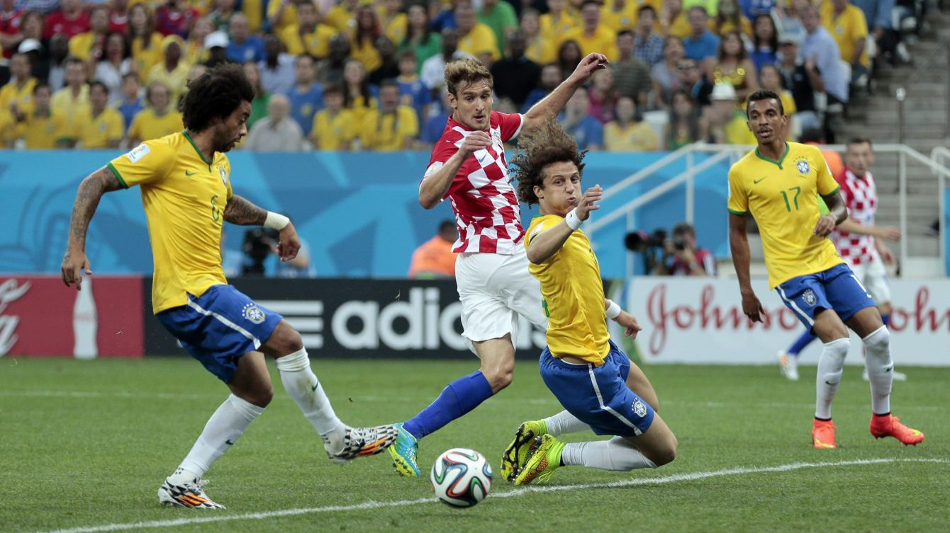 In this June 12, 2014 file photo, Brazil's Marcelo, left, tries to clear the ball but scores on his own goal during the group A World Cup soccer match between Brazil and Croatia, the opening game of the tournament, in the Itaquerao Stadium in Sao Paulo, Brazil. Marcelo looked wide-eyed stunned when he scored the first goal of the World Cup ... against his own team. Hardly the most auspicious of starts for Brazil. But that blooper just 11 minutes in was soon forgiven and forgotten as Brazil went on to win that opening game and the 2014 tournament quickly flowered into a rip-roaring success, confounding doom and gloom merchants who predicted Brazil couldn't pull it off without major protests and problems. (AP Photo/Ivan Sekretarev, File)