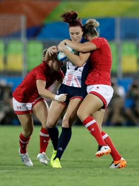 Great Britain's Joanne Watmore, middle, is tackled by Canada's Kayla Moleschi, left, and teammate Kelly Russell, during the women's rugby sevens bronze medal match at the Summer Olympics in Rio de Janeiro, Brazil, Monday, Aug. 8, 2016. (AP Photo/Themba Hadebe)