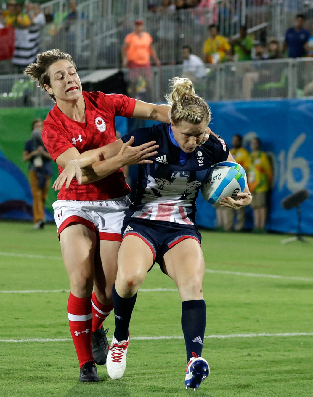 Great Britain's Danielle Waterman, right, avoids a tackle from Canada's Ghislaine Landry, to score a try during the women's rugby sevens bronze medal match at the Summer Olympics in Rio de Janeiro, Brazil, Monday, Aug. 8, 2016. (AP Photo/Themba Hadebe)
