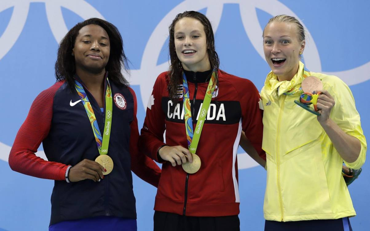 Gold medal winners United States' Simone Manuel and Canada's Penny Oleksiak and Sweden's bronze medal winner Sarah Sjostrom, from left, pose for a photograph during the medal ceremony for the women's 100-meter freestyle final during the swimming competitions at the 2016 Summer Olympics, Friday, Aug. 12, 2016, in Rio de Janeiro, Brazil. (AP Photo/Michael Sohn)