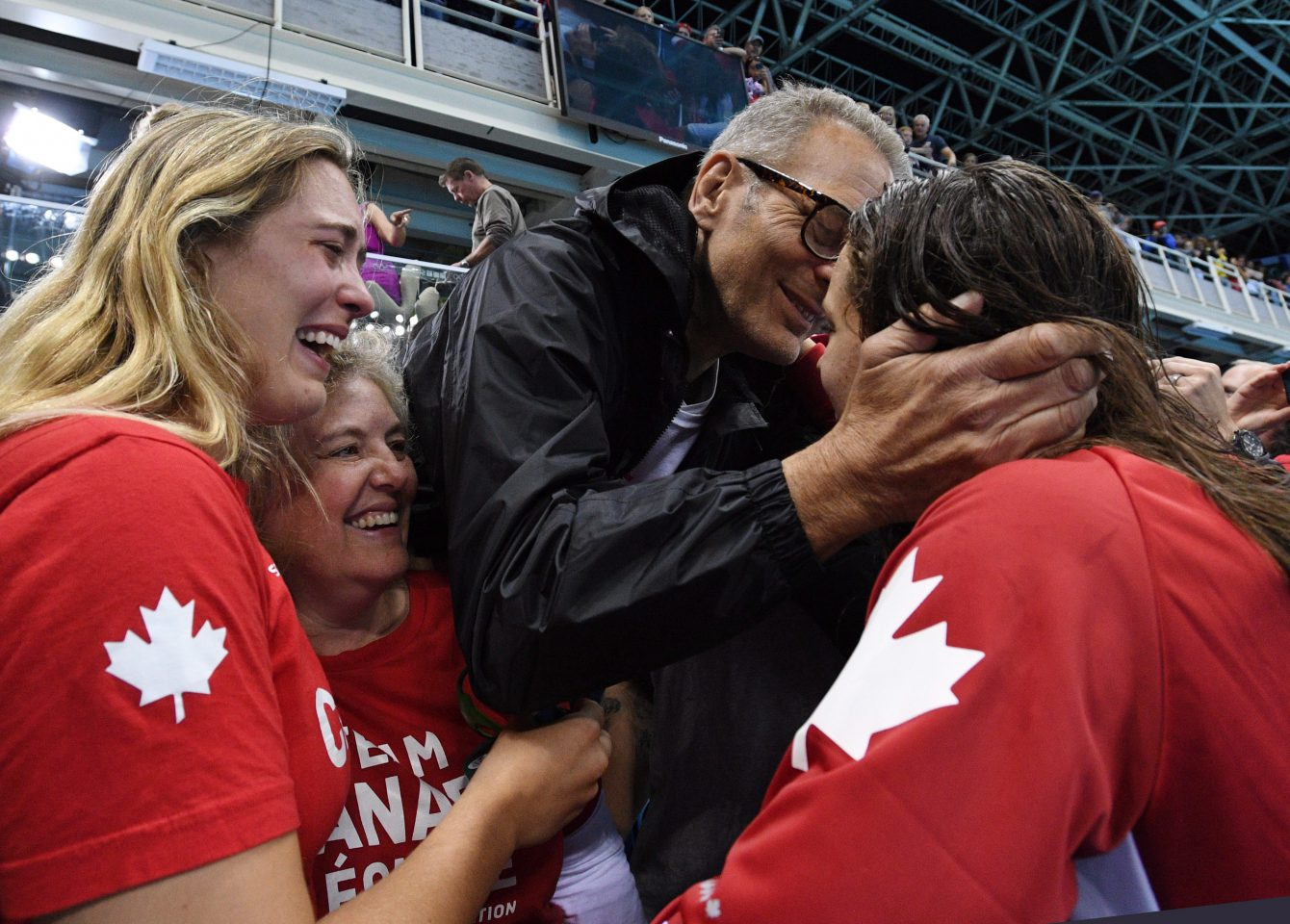 Canada's Penny Oleksiak, right, celebrates with a kiss from her father as her sister and mom look on following her gold-medal performance at the women's 100m freestyle finals during the 2016 Olympic Summer Games in Rio de Janeiro, Brazil, on Friday, Aug. 12, 2016. THE CANADIAN PRESS/Sean Kilpatrick