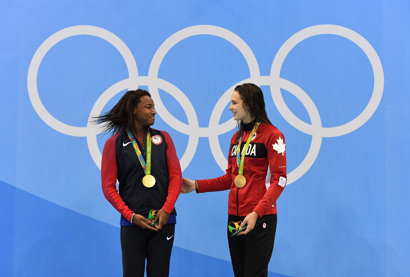 Canada's Penny Oleksiak and the United States' Simone Manuel celebrate their tie for gold in the women's 100m freestyle finals during the 2016 Olympic Summer Games in Rio de Janeiro, Brazil, on Friday, Aug. 12, 2016. THE CANADIAN PRESS/Sean Kilpatrick