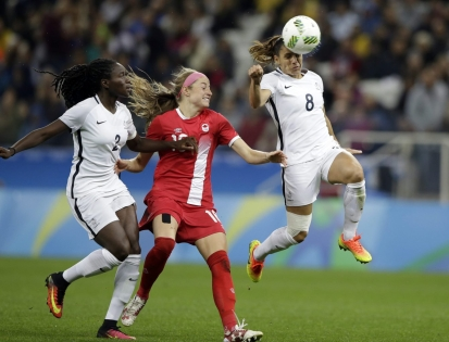 France's Jessica Houara controls the ball with her head past Canada's Janine Beckie during a quarter-final match of the women's Olympic football tournament between Canada and France in Sao Paulo, Brazil, Friday Aug. 12, 2016. At left /Canada's Allysha Chapman.(AP Photo/Nelson Antoine)