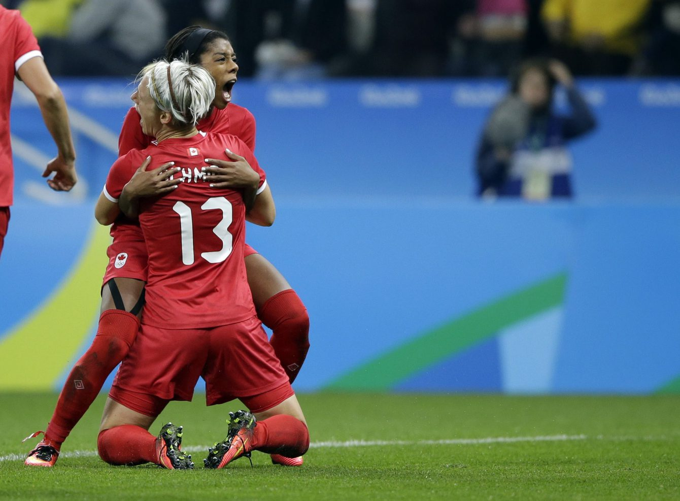 Canada's Sophie Schmidt,, 13, celebrates with teammate Canada's Ashley Lawrence celebrates after scoring her team's first goal during a quarter-final match of the women's Olympic football tournament between Canada and France in Sao Paulo, Brazil, Friday Aug. 12, 2016.(AP Photo/Nelson Antoine)