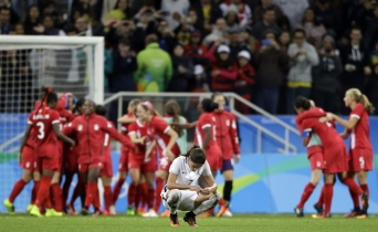 France's Amel Majri reacts in dejection as Canada's players celebrate after beating France in a quarter-final match of the women's Olympic football tournament between Canada and France in Sao Paulo, Brazil, Friday Aug. 12, 2016. Canada's won1-0 and went through to the semi-finals.(AP Photo/Nelson Antoine)