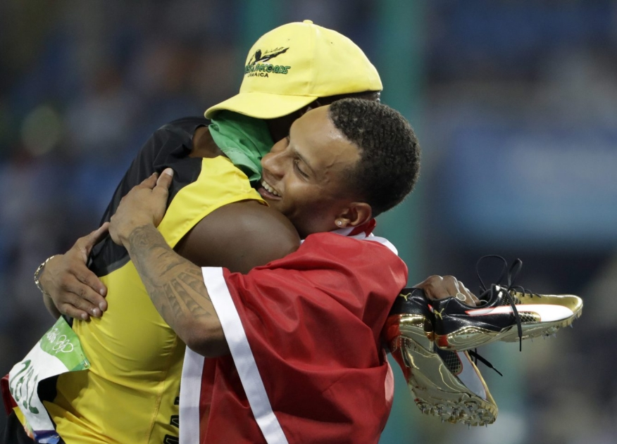 Jamaica's Usain Bolt embraces Canada's Andre De Grasse after they won gold and bronze respectively in the men's 100-meter final during the athletics competitions of the 2016 Summer Olympics at the Olympic stadium in Rio de Janeiro, Brazil, Sunday, Aug. 14, 2016. (AP Photo/David Goldman)