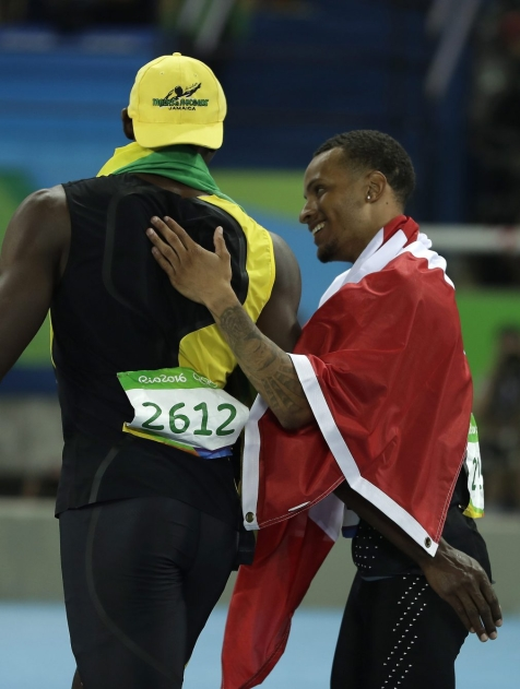 Canada's Andre De Grasse congratulates Jamaica's Usain Bolt after he won the gold medal in the men's 100-meter final during the athletics competitions in the Olympic stadium of the 2016 Summer Olympics in Rio de Janeiro, Brazil, Sunday, Aug. 14, 2016. (AP Photo/Matt Slocum)