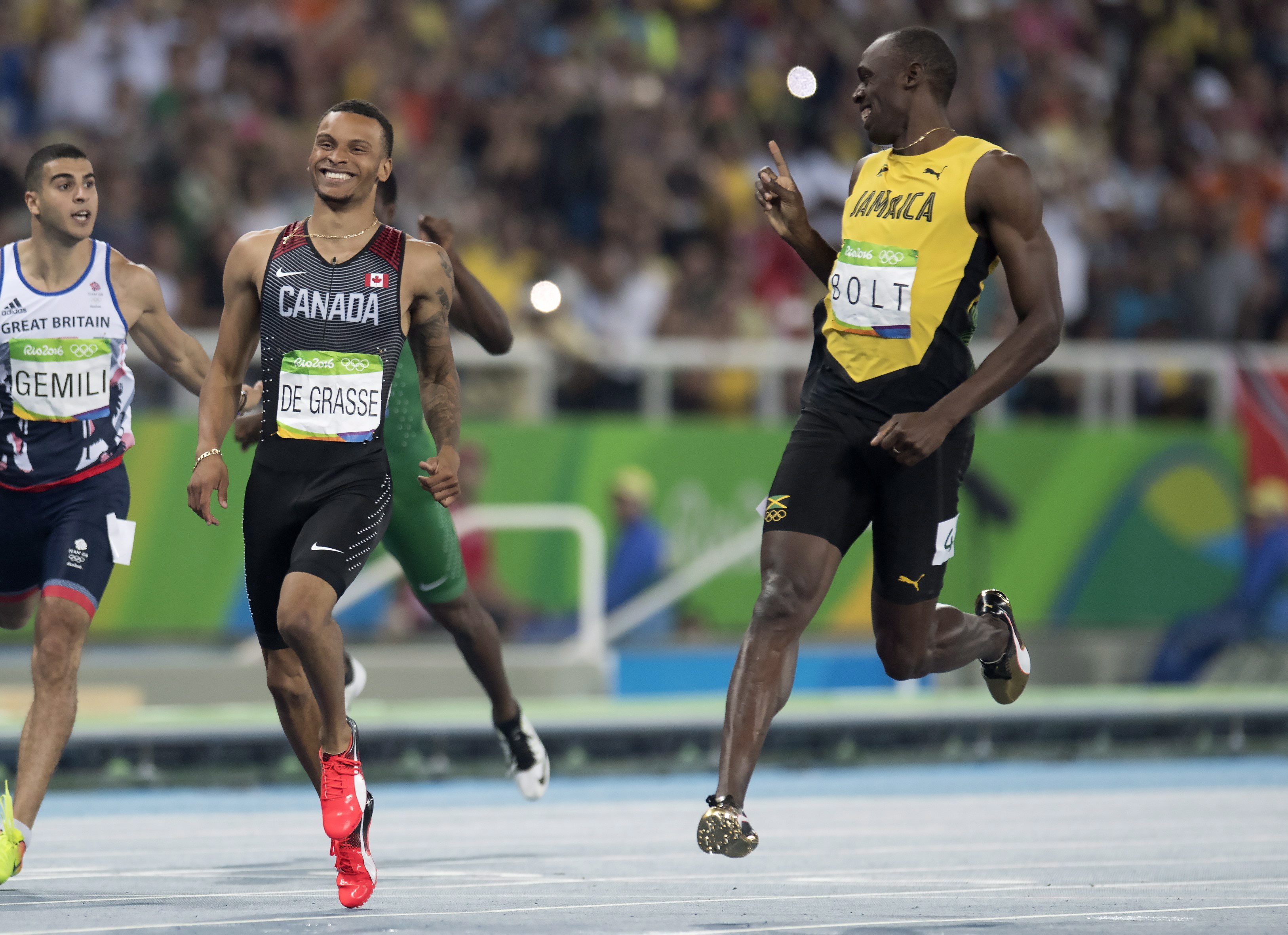 Bolt and De Grasse smiling as they cross the finish line