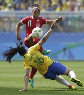 Canada's Desiree Scott, top, kicks the ball under pressure by Brazil's Beatriz during the bronze medal match of the women's Olympic football tournament between Brazil and Canada at the Arena Corinthians stadium in Sao Paulo, Friday Aug. 19, 2016. (AP Photo/Nelson Antoine)
