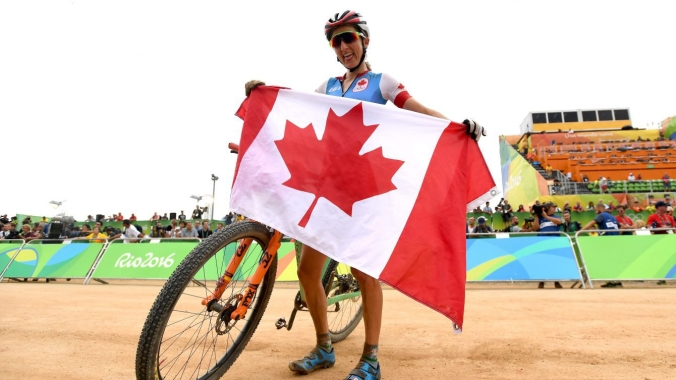 Canada's Catharine Pendrel poses with the Canadian flag as she celebrates winning the bronze medal in the women's mountain bike final at the 2016 Olympic Summer Games in Rio de Janeiro, Brazil on Saturday, Aug. 20, 2016. THE CANADIAN PRESS/Sean Kilpatrick