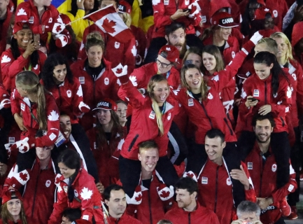 Athetes from Canada, some wearing mittens, march into the closing ceremony in the Maracana stadium at the 2016 Summer Olympics in Rio de Janeiro, Brazil, Sunday, Aug. 21, 2016. (AP Photo/Charlie Riedel)