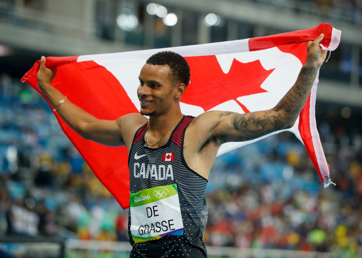 Andre De Grasse holds up Canadian flag