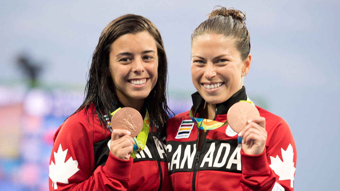 Pair smiling with Olympic bronze medals in hand looking at camera