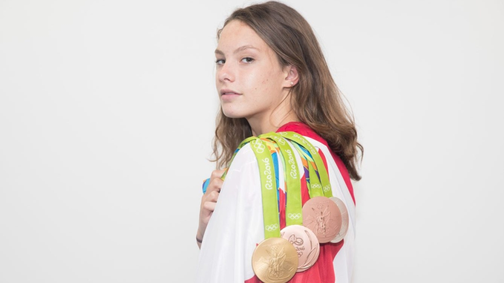 Canada's Penny Oleksiak poses with her medals on the flag at the Olympic games in Rio de Janeiro, Brazil, Sunday August 21, 2016. COC Photo/Mark Blinch