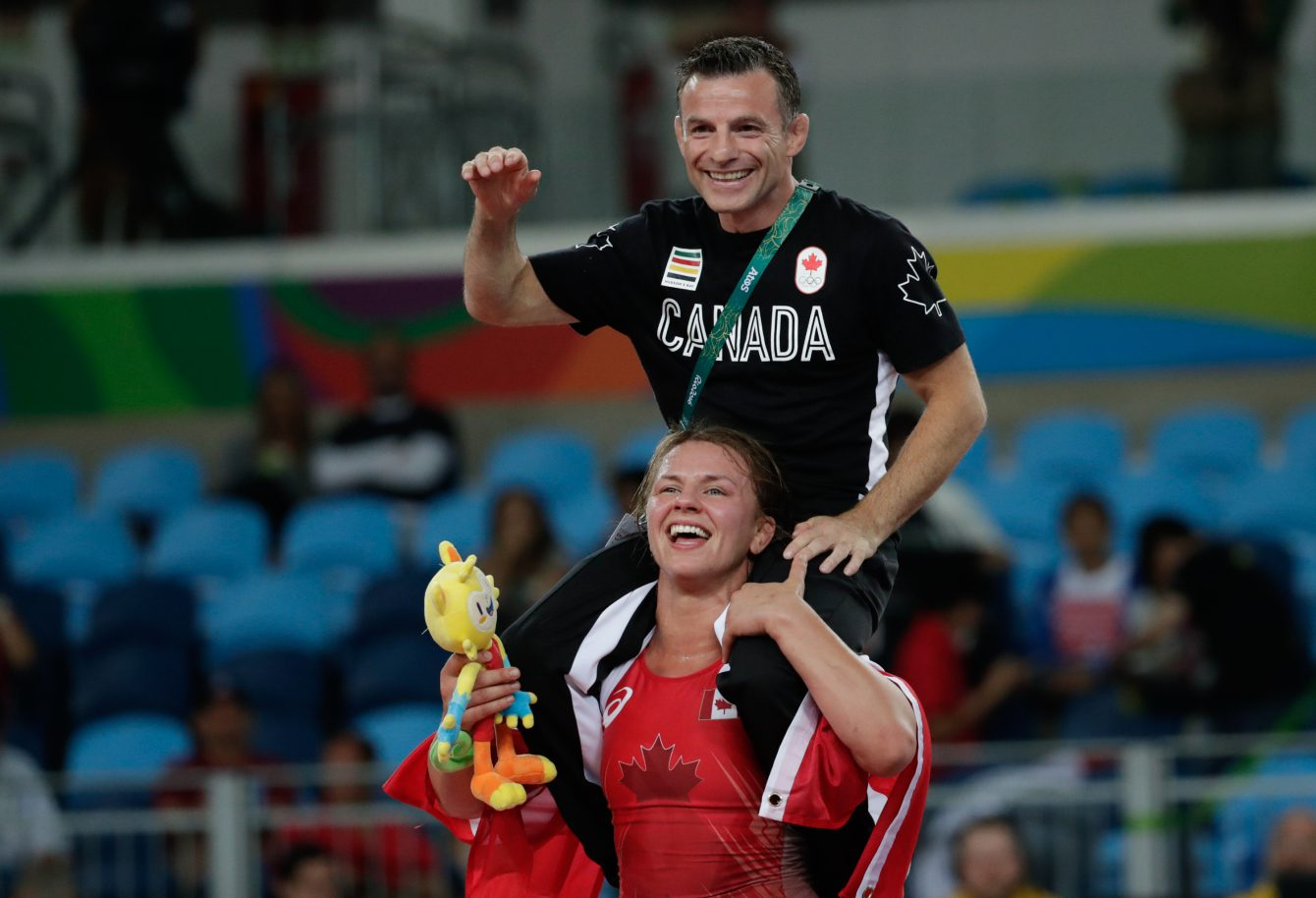 Erica Wiebe carries coach Paul Ragusa after after winning the gold medal during the women's 75kg freestyle wrestling competition at the 2016 Summer Olympics in Rio de Janeiro, Brazil, Thursday, Aug. 18, 2016. photo/ David Jackson