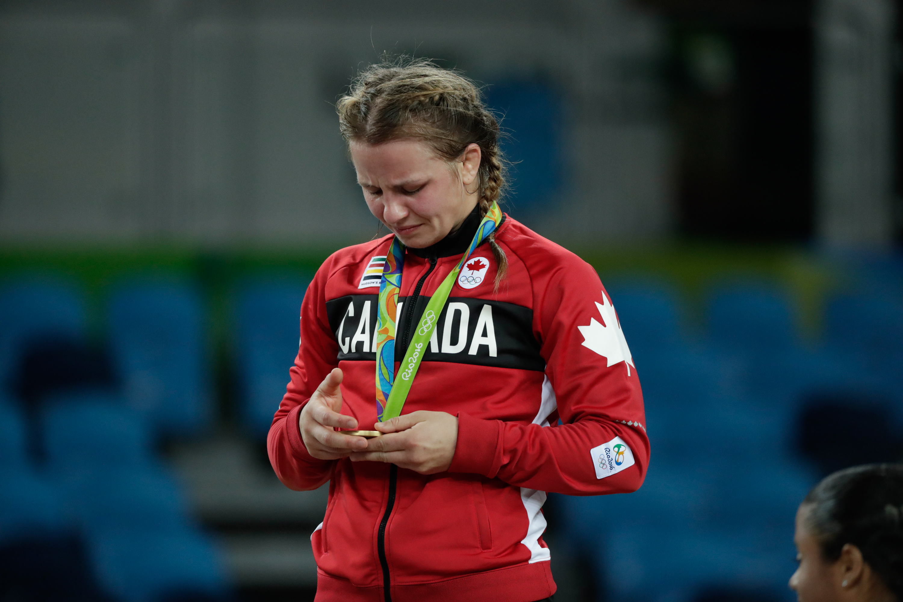 Erica Wiebe looks down at her gold medal while standing on the podium at Rio 2016 (COC/David Jackson)