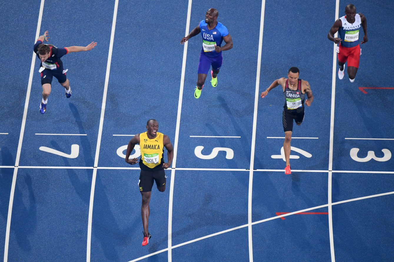 Jamaica's Usain Bolt (2R) crosses the finish line to win the Men's 200m Final during the athletics event at the Rio 2016 Olympic Games at the Olympic Stadium in Rio de Janeiro on August 18, 2016, with Andre De Grasse of Canada finishing second. / AFP / Antonin THUILLIER (Photo credit should read ANTONIN THUILLIER/AFP/Getty Images)