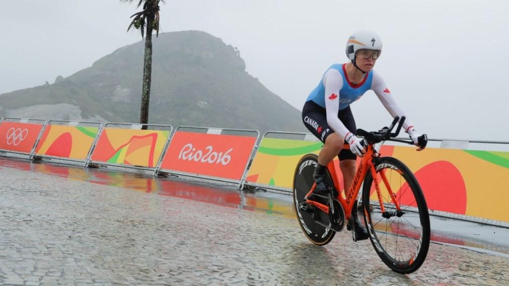 Karol Ann Canuel bikes in the rain in Rio