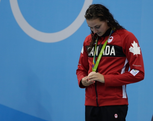 Masse looking down at her Olympic medal