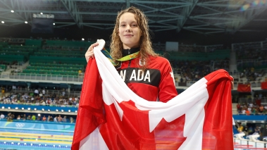 Penny Oleksiak holds the flag after winning silver in the 100m butterfly on August 7, 2016 during Rio 2016.