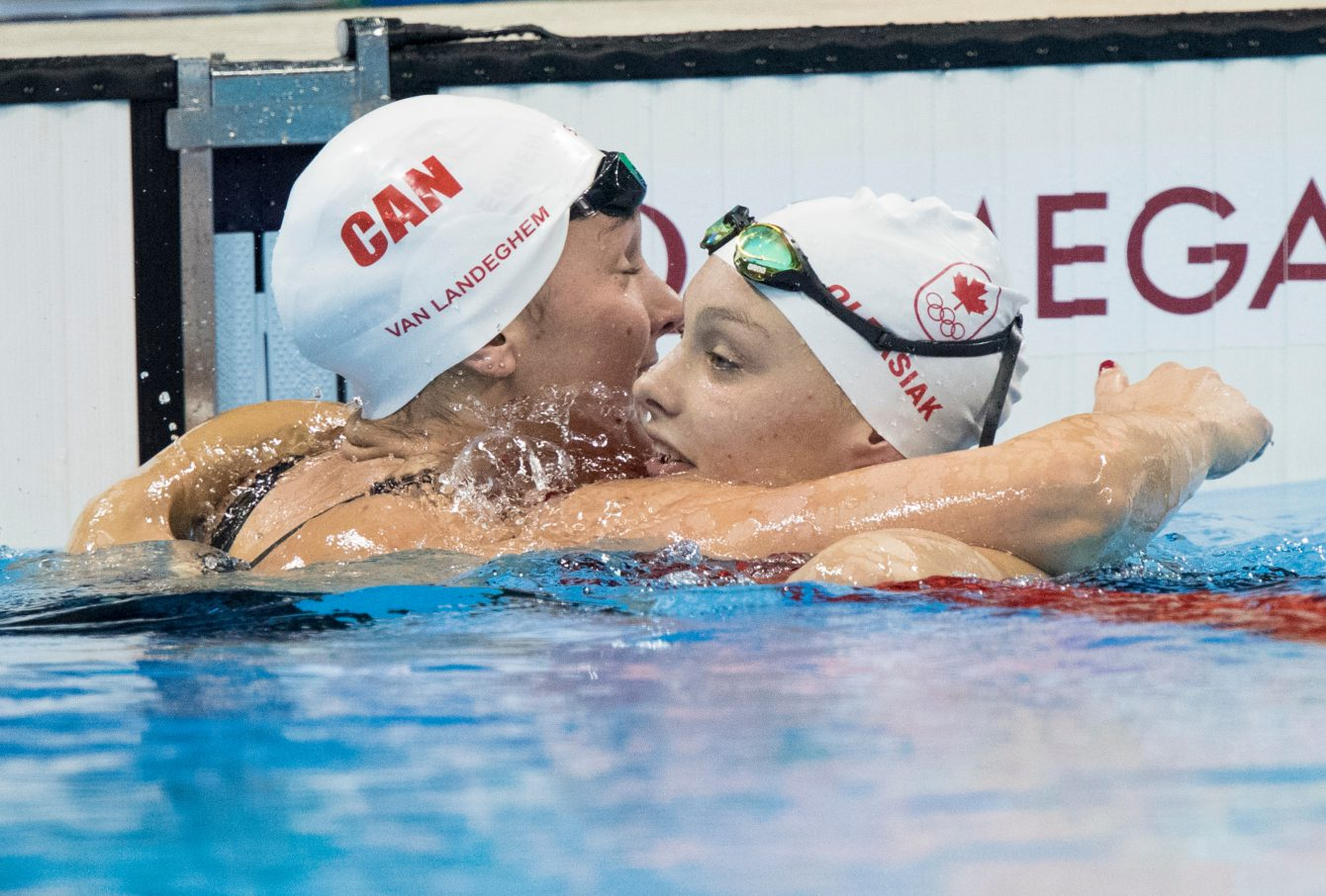 Canada's Penny Oleksiak, right, gets a hug from teammate Chantal Van Landeghem after Oleksiak qualified for the women's 100m freestyle final at the Olympic games in Rio de Janeiro, Brazil, Wednesday, August 10, 2016. COC Photo by Jason Ransom