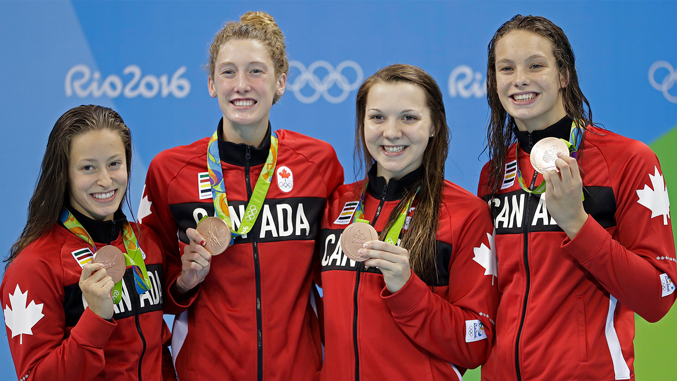 Canada's Katerine Savard, Taylor Ruck, Brittany Maclean and Penny Oleksiak, from left, hold up their bronze medals during the women's 4 x 200-meter freestyle relay medals ceremony during the swimming competitions at the 2016 Summer Olympics, Thursday, Aug. 11, 2016, in Rio de Janeiro, Brazil.
