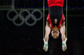 Scott Morgan performs on the rings during men's artistic gymnastics