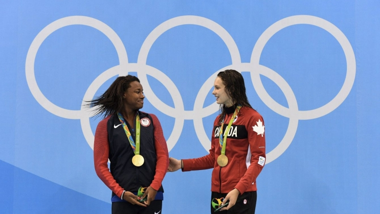 Penny Oleksiak (right) and Simone Manuel atop the Olympic podium at Rio 2016 on August 11, 2016.
