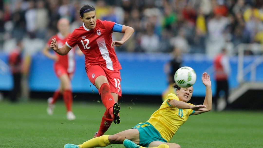 Sinclair kicking ball past sliding defender