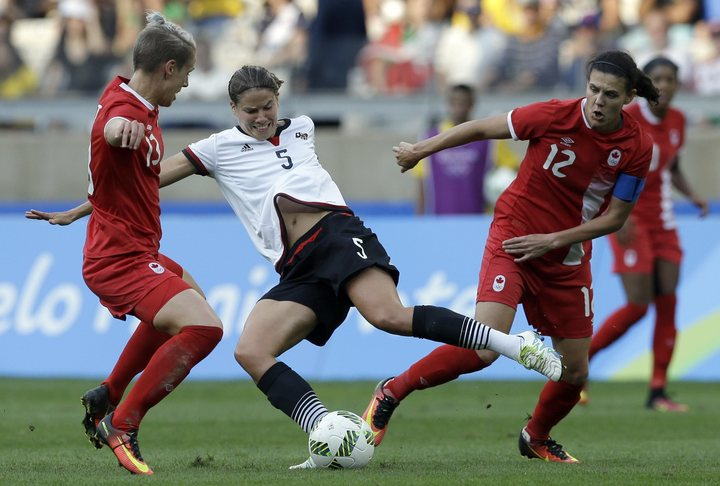 Germany's Annike Krahn controls the ball next to Canada's Sophie Schmidt, left, and Christine Sinclair during a semifinal match of the women's Olympic football tournament between Germany and Canada at the Mineirao Stadium in Belo Horizonte, Brazil, Tuesday, Aug. 16, 2016. (AP Photo/Leo Correa)