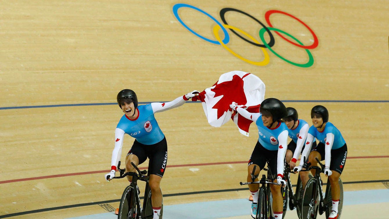 Canada's team pursuit riders lift the flag following their Olympic bronze medal win over New Zealand in Rio de Janeiro on August 13, 2016.