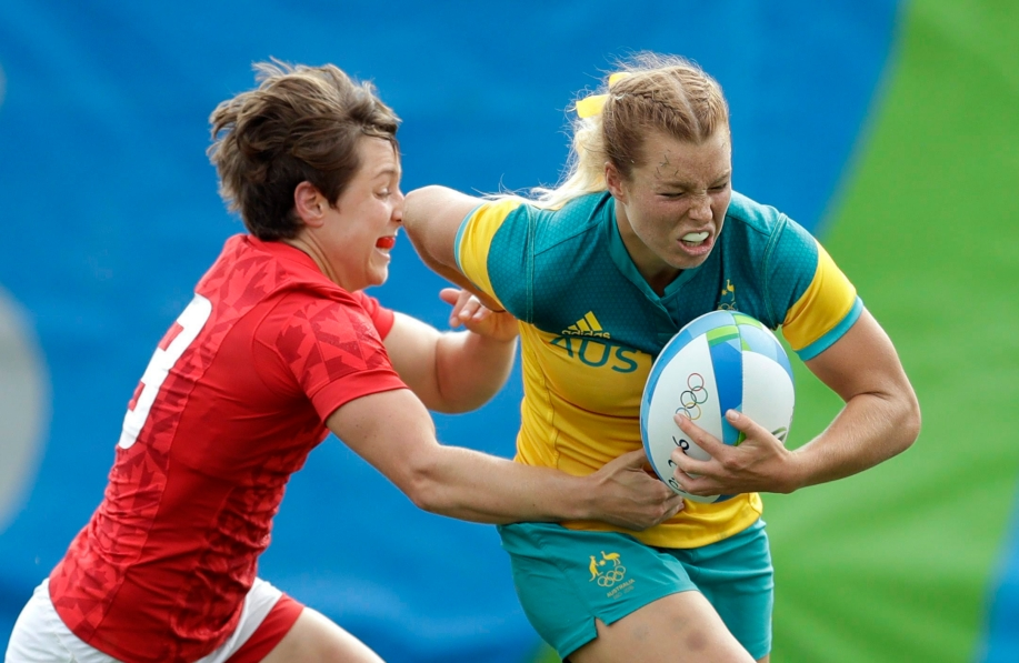 Australia's Emma Tonegato, avoids a tackled by Canada's Ghislaine Landry, during the women's rugby sevens semi final match at the Summer Olympics in Rio de Janeiro, Brazil, Monday, Aug. 8, 2016. (AP Photo/Themba Hadebe)