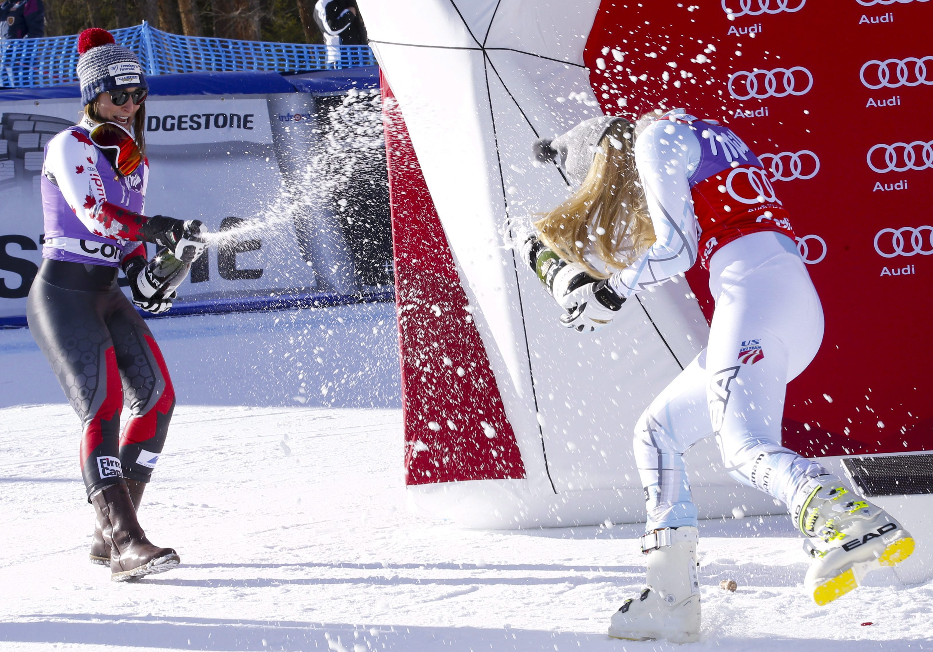 Lindsey Vonn, of the United States, right, sprays sparkling wine with second placed Canada's Larisa Yurkiw, after winning an alpine ski, women's World Cup downhill, in Cortina D'Ampezzo, Italy, Saturday, Jan. 23, 2016. (AP Photo/Armando Trovati)
