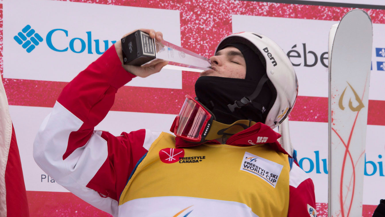 Mikael Kinsgsbury kisses his trophy as he celebrates his victory at the moguls World Cup on January 21, 2017 in St-Come, Que. THE CANADIAN PRESS/Jacques Boissinot