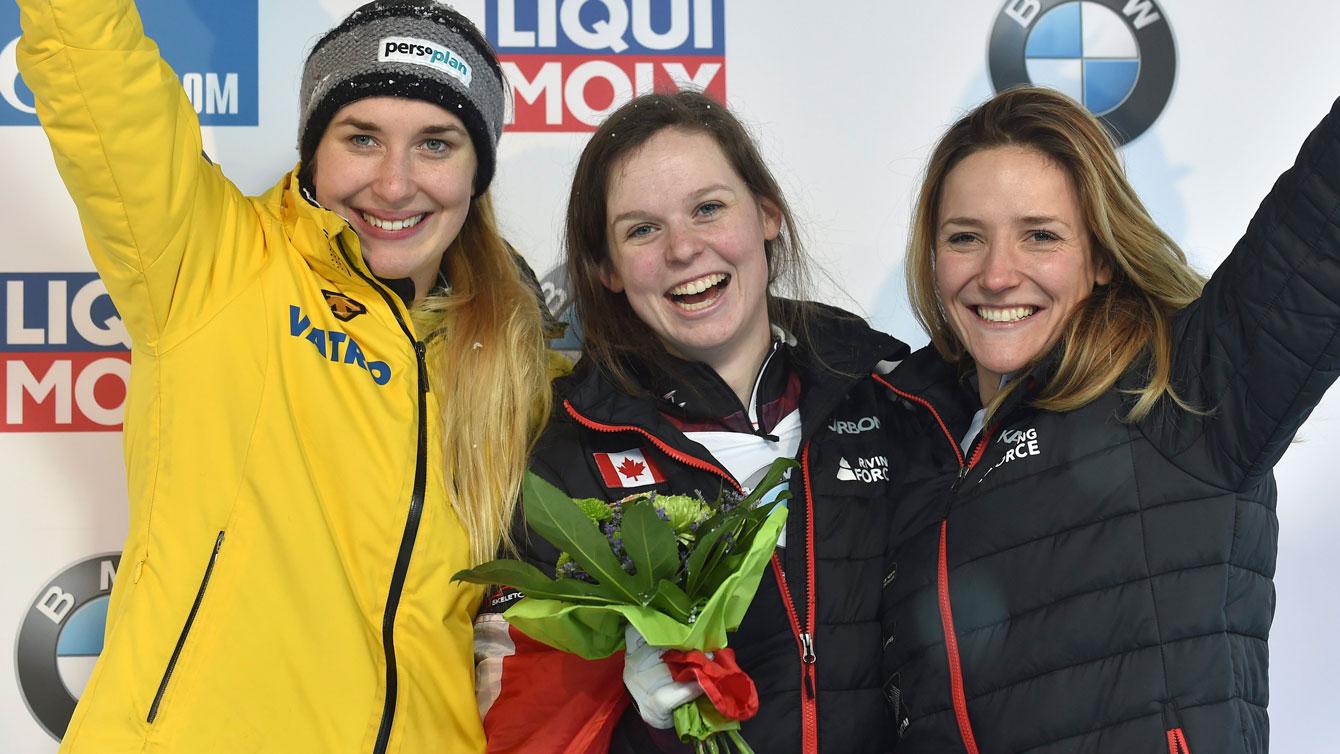 Elisabeth Vathje and Mirela Rahneva celebrate finishing first and third respectively at the Skeleton World Cup in Winterberg, Germany on Jan. 15, 2017. (Caroline Seidel/dpa via AP)