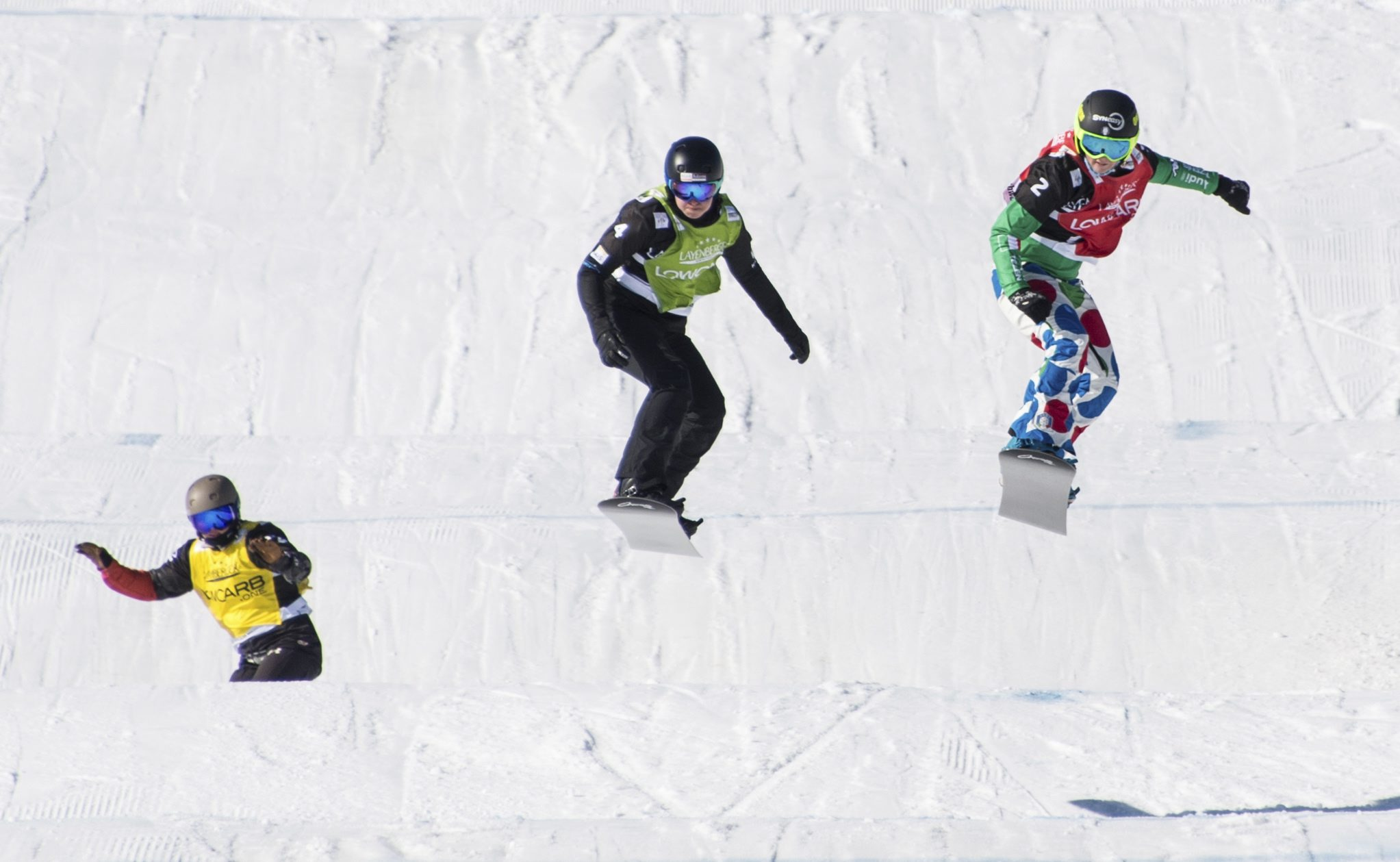 Winner Michaela Moioli from Italy, right, second placed Belle Brockhoff from Australia, center, (2nd place, c) and third placed Meryeta Odine from Canada, left, speed down the track during the Ladies' Snowboard Cross World Cup at Feldberg mountain in the Black Forest region, Germany,, Saturday, Feb. 11, 2017. ( Patrick Seeger/dpa via AP)