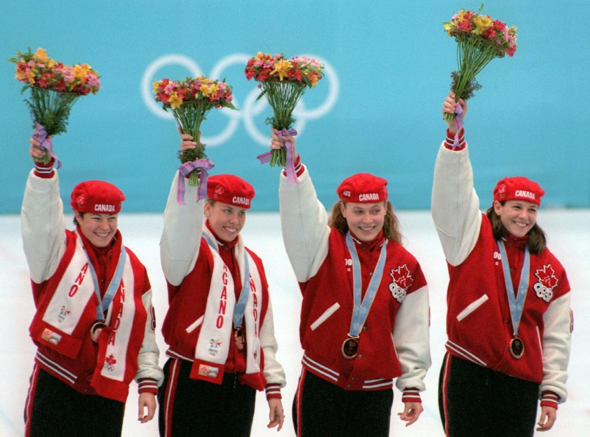 Canada's Short Track Speed Skating relay team Annie Perreault, Tania Vicent, Christine Boudrias and Isabelle Charest, left to right, wave from the podium after winning the Olympic bronze medal in the ladies 3,000m relay Tuesday in Nagano. (CP PHOTO) 1998 (stf/Paul Chiasson)