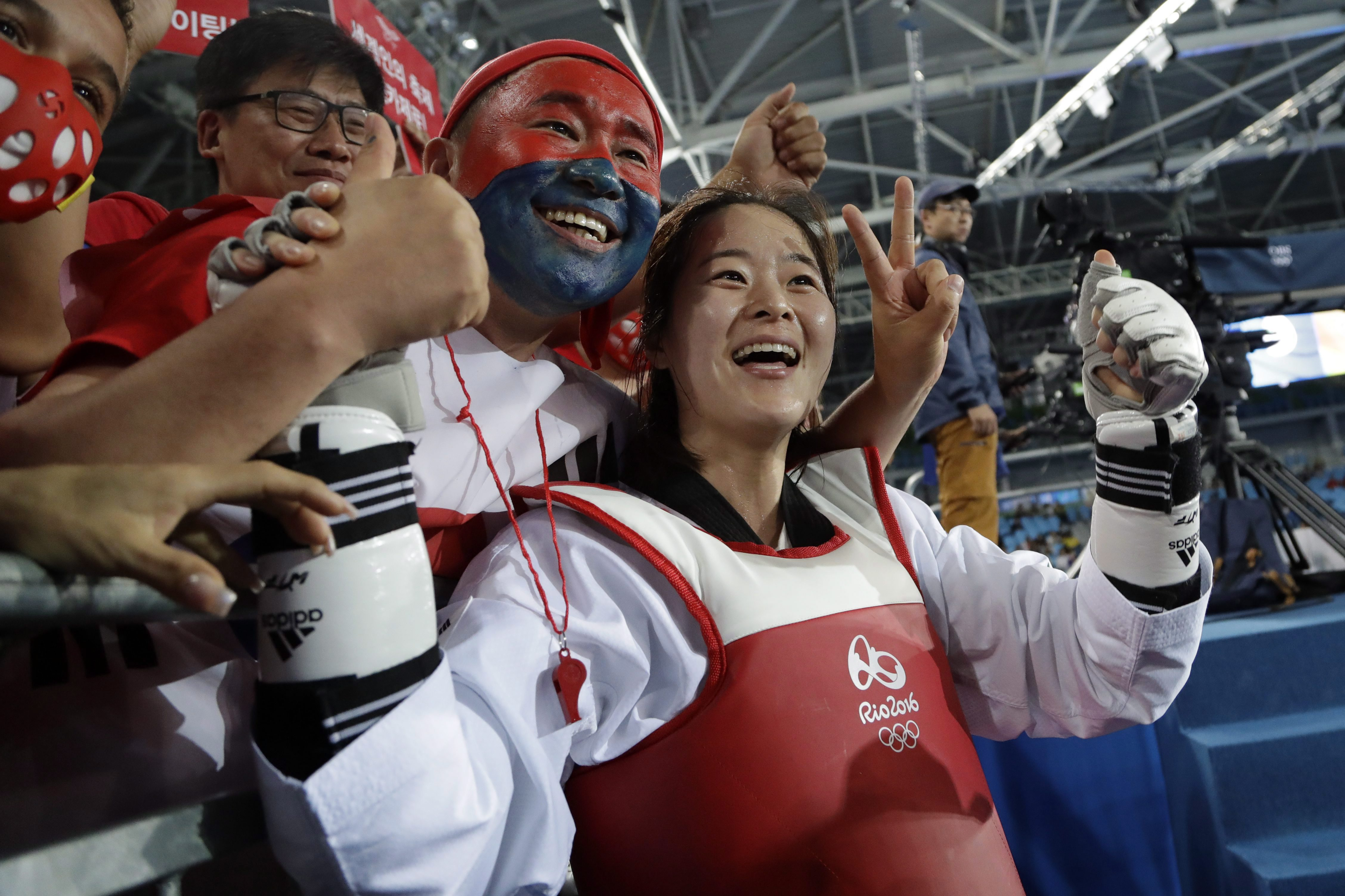 Oh Hye-ri of South Korea celebrates with fans after winning the gold medal in the women's 67 kg taekwondo competition at the 2016 Summer Olympics in Rio de Janeiro, Brazil, Friday, Aug. 19, 2016. (AP Photo/Gregory Bull)
