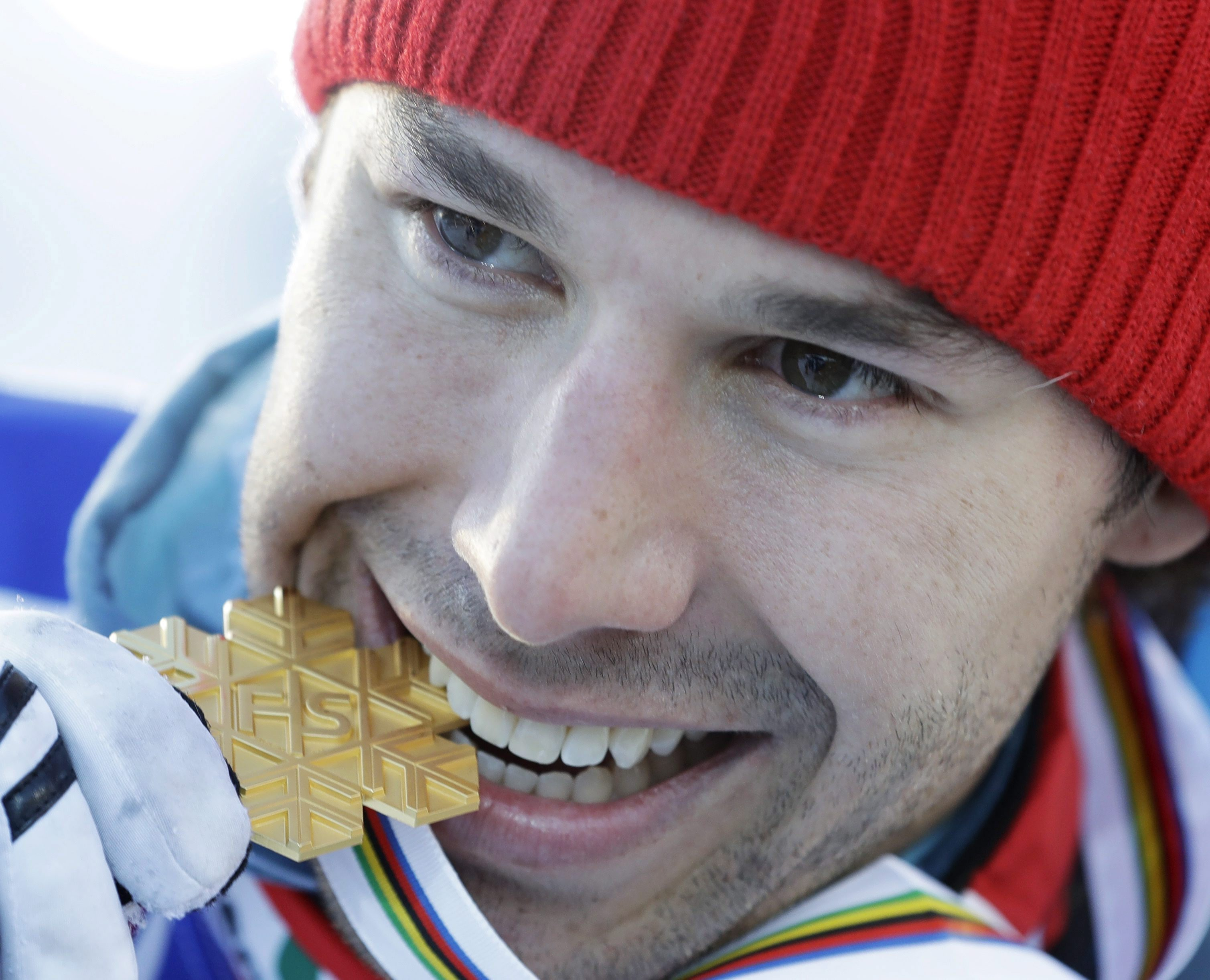 Canada's Alex Harvey bites his gold medal after winning the men's 50 km race during the 2017 Nordic Skiing World Championships in Lahti, Finland, Sunday, March 5, 2017. (AP Photo/Matthias Schrader)