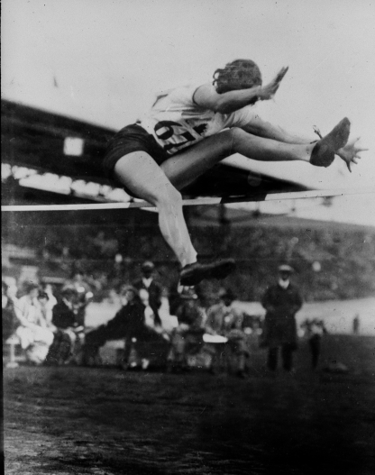 Black and white image of Ethel Catherwood during her high jump. Her left leg is going over the high jump bar with her right about to follow.