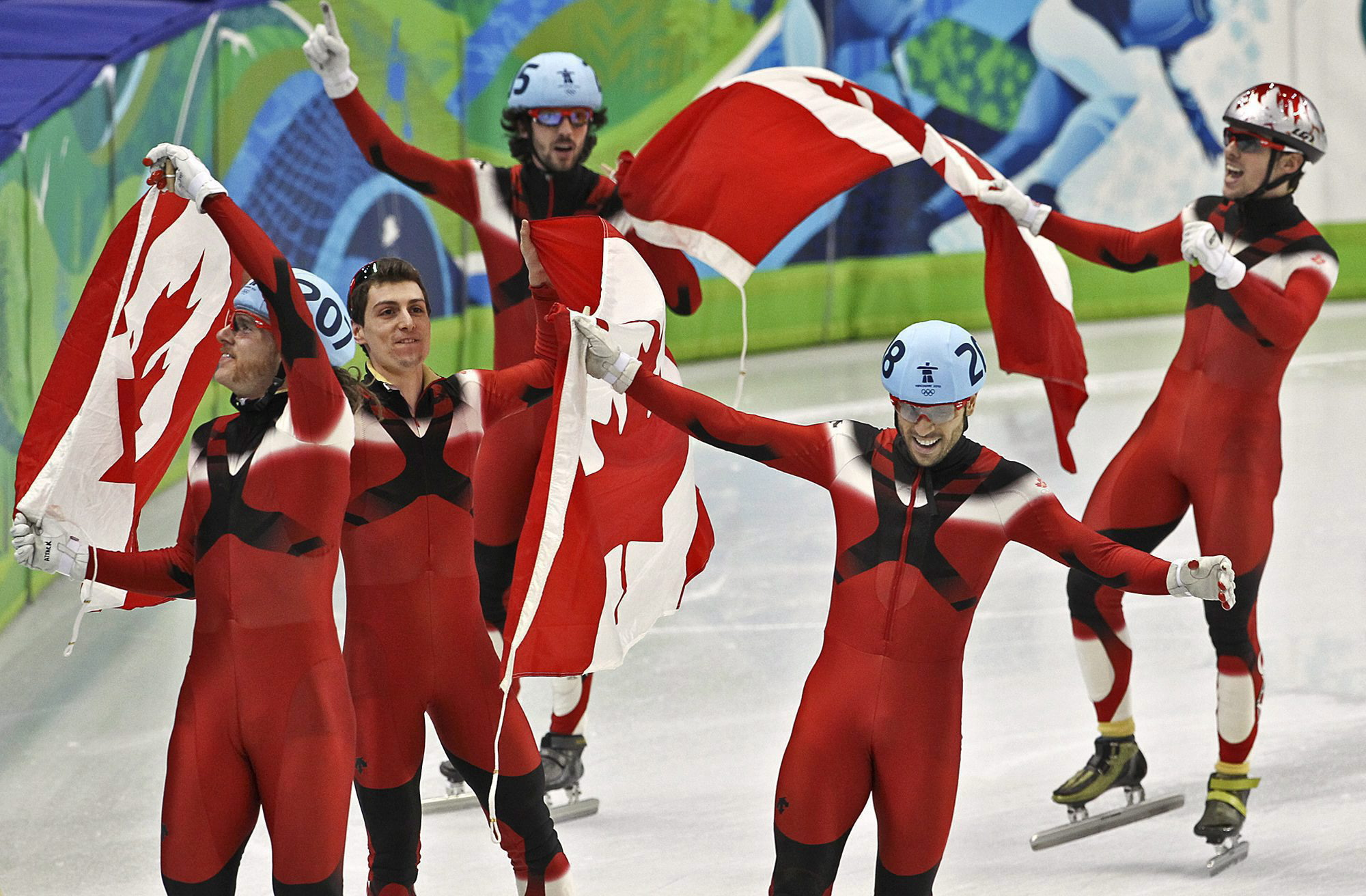 Short track speed skaters carry Canadian flag